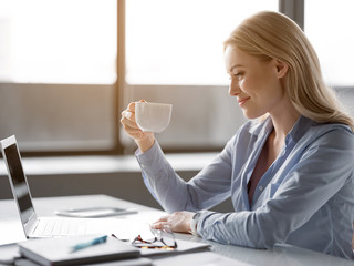 Happy young woman is drinking hot beverage at workplace. She is looking at cup with joy and smiling