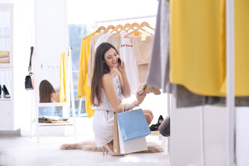 Young beautiful woman talking on mobile phone while shopping in store