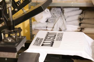 Young man printing on t-shirt at workshop