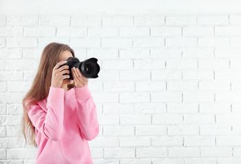 Female photographer with camera on brick background