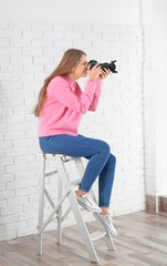 Female photographer with camera sitting on chair indoors