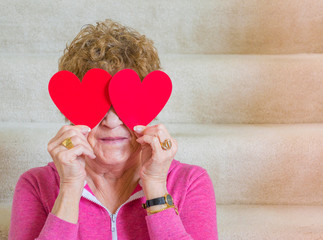 Smiling middle aged Caucasian woman holding red paper hearts over her eyes while sitting on carpeted stairs