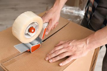 Young man packing moving box indoors, closeup