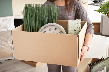 Young woman holding moving box with office stuff indoors, closeup
