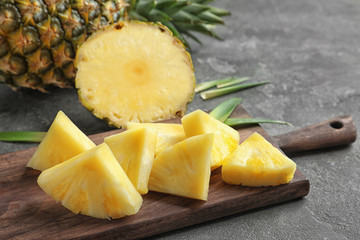 Wooden board with fresh sliced pineapple, closeup