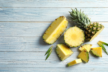 Flat lay composition with fresh sliced pineapple on wooden background