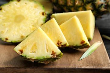 Fresh sliced pineapple on wooden board, closeup