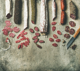 Variety of Spanish or Italian cured meat sausages. Flat-lay of fuets and salamies cut in slices over rough grey concrete background, top view, copy space