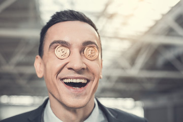 Portrait of satisfied male worker holding bitcoins on eyes. He looking at camera. Glad rich employer concept
