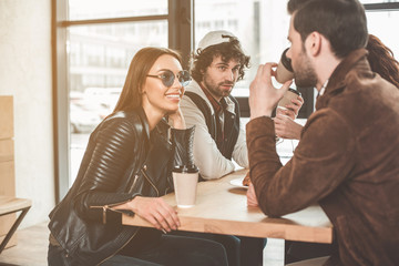 Young man is telling interesting story to his friends. Woman is listening to him with excitement and smiling. People are sitting at table in cafeteria