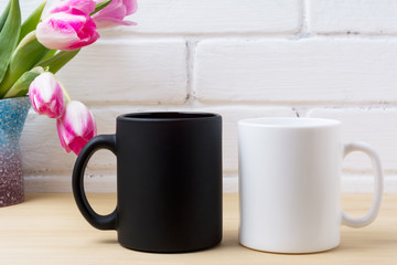 Black coffee mug and white cappuccino cup mockup with pink tulips