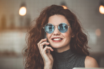 Portrait of excited young woman calling on mobile phone and smiling. She is wearing stylish sunglasses