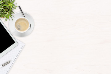 White wooden office desk top view with office utensils, plant and cup of coffee