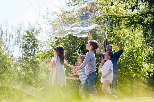 Middle-aged bearded animator presenting his soap bubble show to little children while spending summer day at green park illuminated with sunbeams