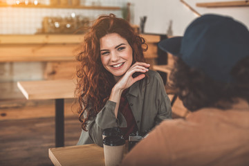 Portrait of joyful young woman flirting with man in cafe. She is looking at boyfriend playfully and smiling