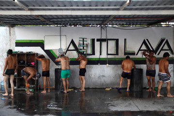 Central American migrants, moving in a caravan through Mexico, bathe at a car wash in Irapuato