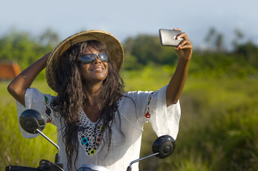 young attractive black afro American tourist woman in Asian traditional hat riding motorbike taking selfie photo with mobile phone smiling happy