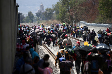 Central American migrants, moving in a caravan through Mexico, disembark from from a freight train as they walk on a railway track in Irapuato