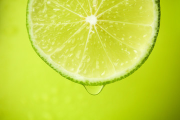 Close-up of a slice of lime, a drop of water falls. The fruit gives off freshness and juice filling.