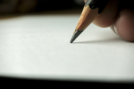Writing on white paper with a pencil