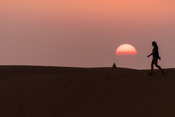 people walking in Mui Ne sand dunes at sunset in Vietnam