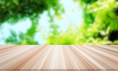Design concept - Empty wood table top with green leaf background for display or montage product