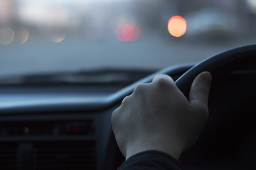 Male hand on the steering wheel, view from the windshield, bokeh