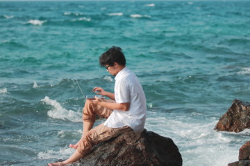 Young Asian man traveler using laptop on the rock of natural seashore. Vacations summer concept.