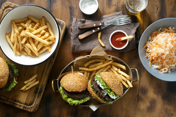Delicious outdoor table with burger, french fries and salad on wooden table with beer, top view. Outdoors food Concept