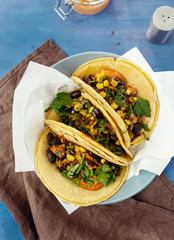 Top view vegetarian healthy corn tortillas with vegetables on wooden table