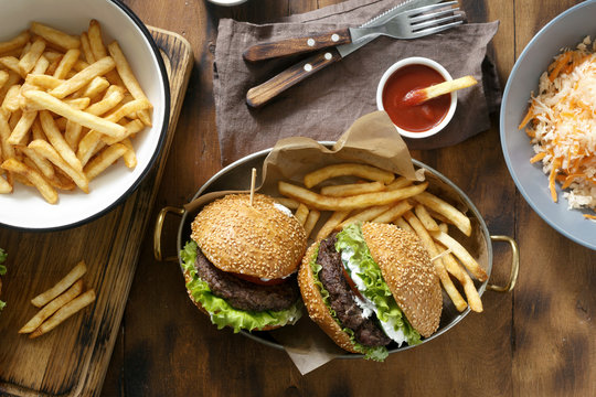 Top view outdoor table with burger, french fries and salad on wooden table, top view