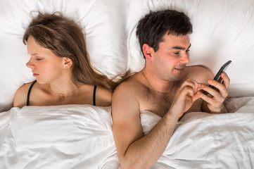 Young man using mobile phone, while his wife sleep at night