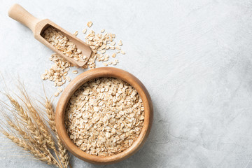 Organic rolled oats in wooden bowl on concrete background. Top view with copy space for text. Concept of healthy lifestyle, healthy eating, dieting, sport and fitness menu