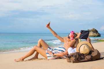 Couple relaxing on the beach and using tech devices