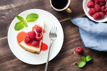 Cheesecake with raspberries and berry sauce on wooden table. Top view, selective focus