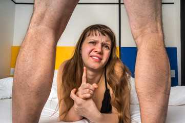 Woman in bed looking what's between man's legs