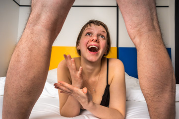 Woman in bed looking what's between man's legs