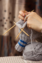 hands of woman knitting a sock with bamboo needles