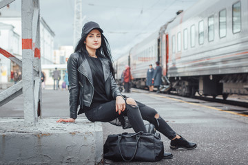Woman in black dress on the railroad station