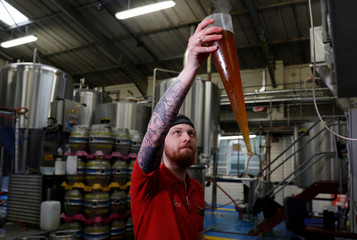 A worker checks the clarity of the liquid from a mash tun at the Windsor and Eton brewery in Windsor