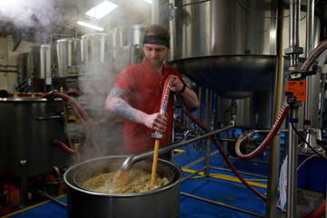 A worker drains liquid from a mash tun at the Windsor and Eton brewery in Windsor