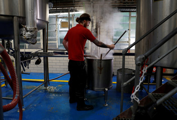A worker stirs liquid from a mash tun and hops at the Windsor and Eton brewery in Windsor