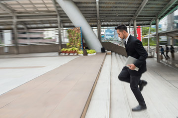 Businessman running in hurry at town