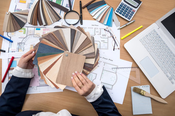 The designer works in the office with samples of colors, a laptop and a plan of the building