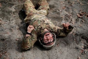 A U.S. Military cadet crawls under a barbed wire obstacle as he competes in the 50th annual Sandhurst Military Skills Competition at the United States Military Academy at West Point, New York