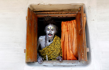 A devotee, dressed as Hindu God Shiva, looks out from a window as he waits to perform during the annual Shiva Gajan religious festival on the outskirts of Agartala