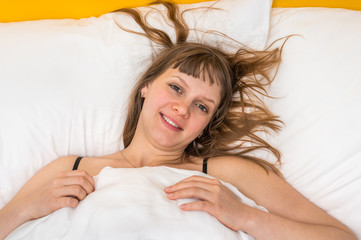 Attractive smiling woman in bed at morning