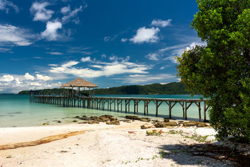 Tropical landscape of Koh Rong Samloem island with turquoise water and pier in the distance. Cambodia, asia.