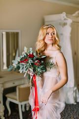 Portrait of blonde sexy bride in white underwear with bouquet.  Luxurious apartments background.