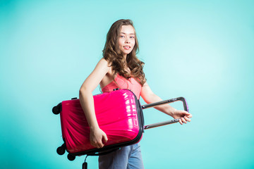 Woman traveler with suitcase on color background. Beautiful brunette girl in pink top and jeans stands on blue background